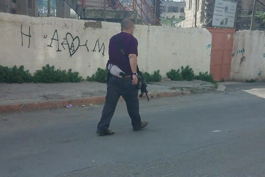 Image: Israeli settler walking by a school with a rifle and pistol (Photo: CPT)
