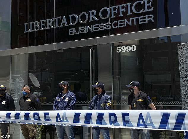 Police stand guard the entrance of Dr. Leopoldo Luque's practice in Buenos Aires, Argentina