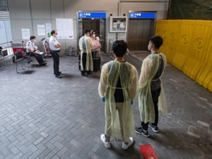 Workers wearing personal protective equipment (PPE) assist arriving passengers to board a bus to a coronavirus testing facility in Hong Kong.