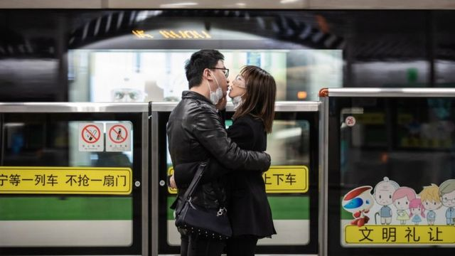 A couple kiss each other with their masks off while waiting for a train in Shanghai. 24 February