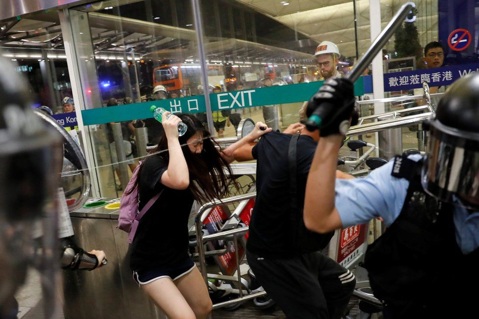 Riot police use pepper spray to disperse anti-extradition bill protesters during a mass demonstration after a woman was shot in the eye, at the Hong Kong international airport