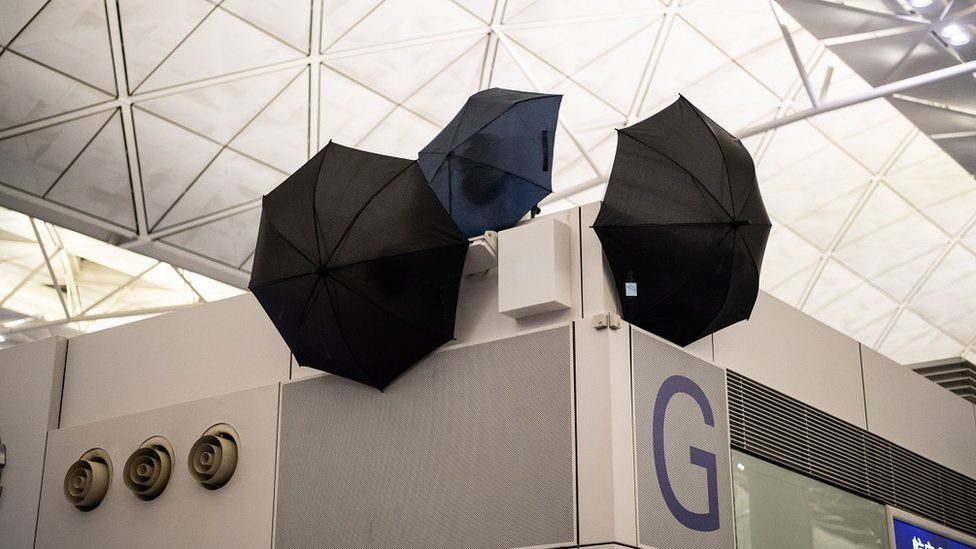 Umbrellas block CCTV cameras as anti-government protesters attend a demonstration