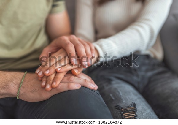 Close up woman and man in love sitting on couch two people holding hands. Symbol sign sincere feelings, compassion, loved one, say sorry. Reliable person, trusted friend, true friendship concept