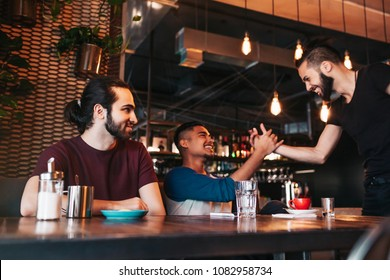 Multiracial men meeting their friend in lounge bar. Real emotions of best friends happy to see each other. Friendship