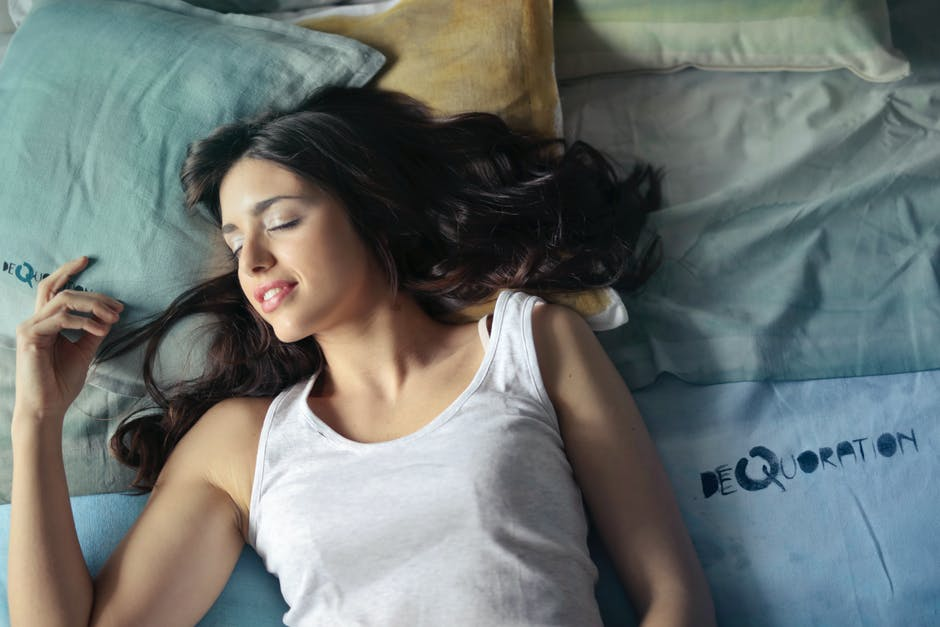 Photo of Woman in White Tank Top Lying on Bed