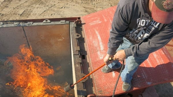 A man uses a blow torch to light the fire