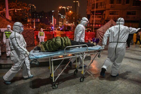 Các nhân viên y tế mặc quần áo bảo hộ để giúp ngăn chặn sự lây lan của một loại virus chết người bắt đầu trong thành phố, đang vận chuyển một bệnh nhân tại Bệnh viện Chữ thập đỏ Vũ Hán ở Vũ Hán, Trung Quốc, vào ngày 25 tháng 1 năm 2020. (Ảnh: Hector Retamal / AFP qua Getty Images)
