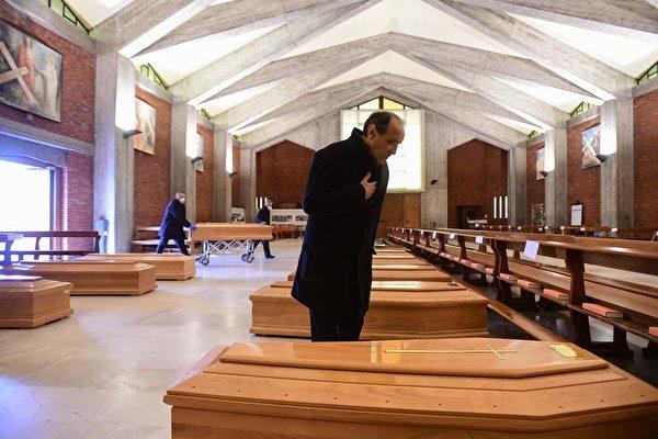 Nhà thờ San Giuseppe ở Seriate chứa quan tài của những người tử vong do virus ĐCSTQ. Vị linh mục đứng cạnh một trong những chiếc quan tài và cầu nguyện. (Ảnh: Getty)