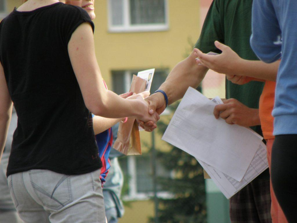 People shaking hands in front of a house while holding documents.