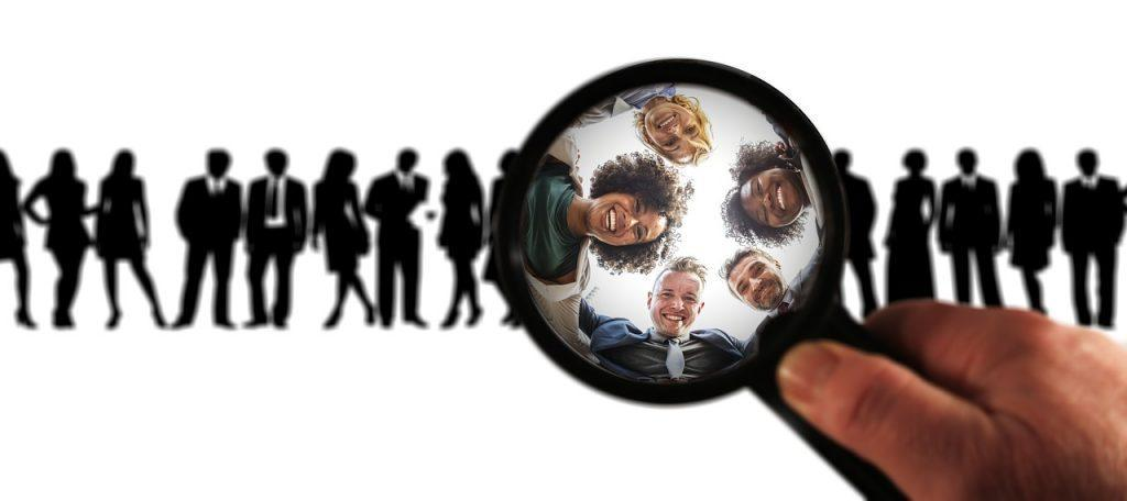 A person using a magnifying glass to pick a small group of people out a larger one.