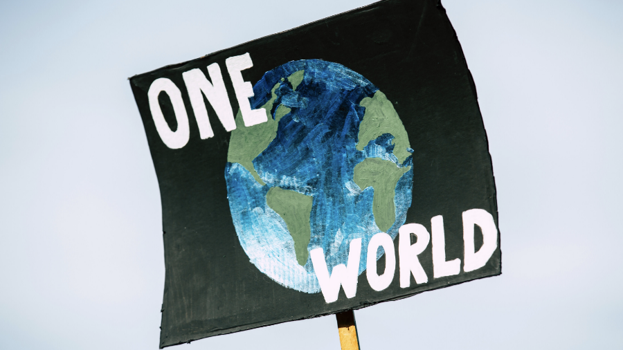 "A painted poster with an image of the earth and the words, ""One World."""