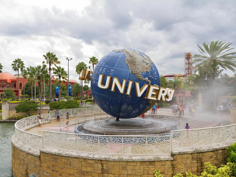 Entrance to the Universal Studios section in the Orlando resort, with the landmark globe sign in the foreground and visitor around it.