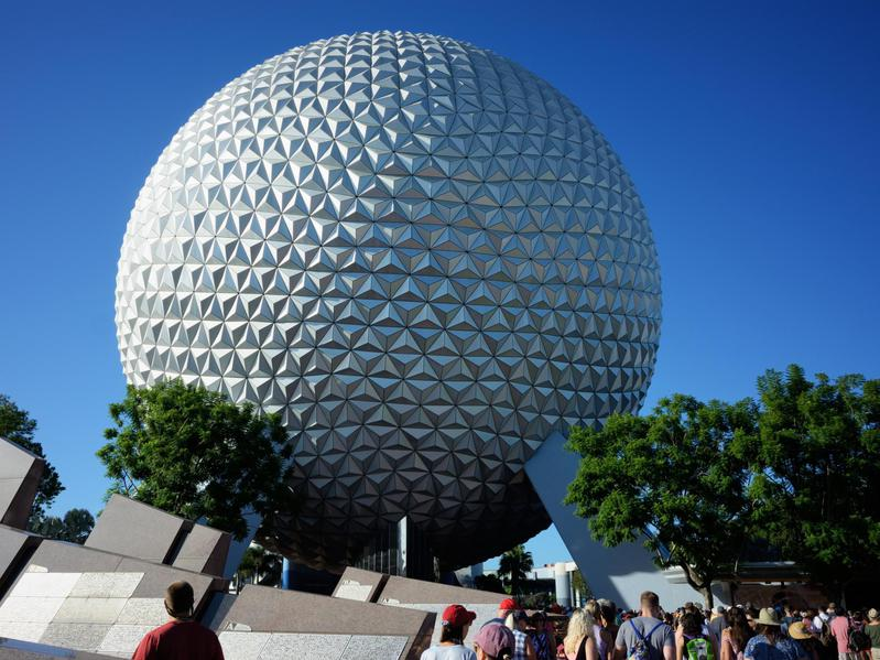 Tourists walk toward Spaceship Earth globe at the Epcot Park in Orlando