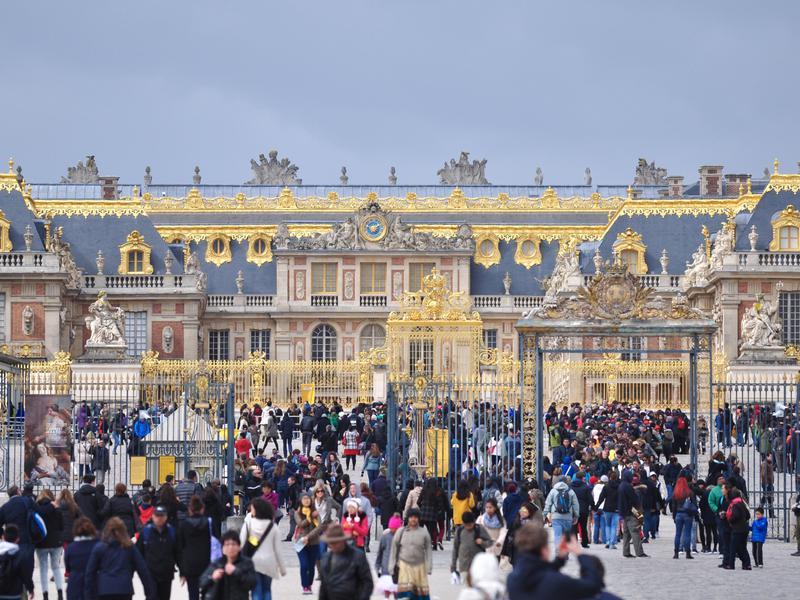 Tourists waiting to visit Versailles Palace, France.