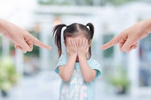 Pais apontando o dedo para filha pequena