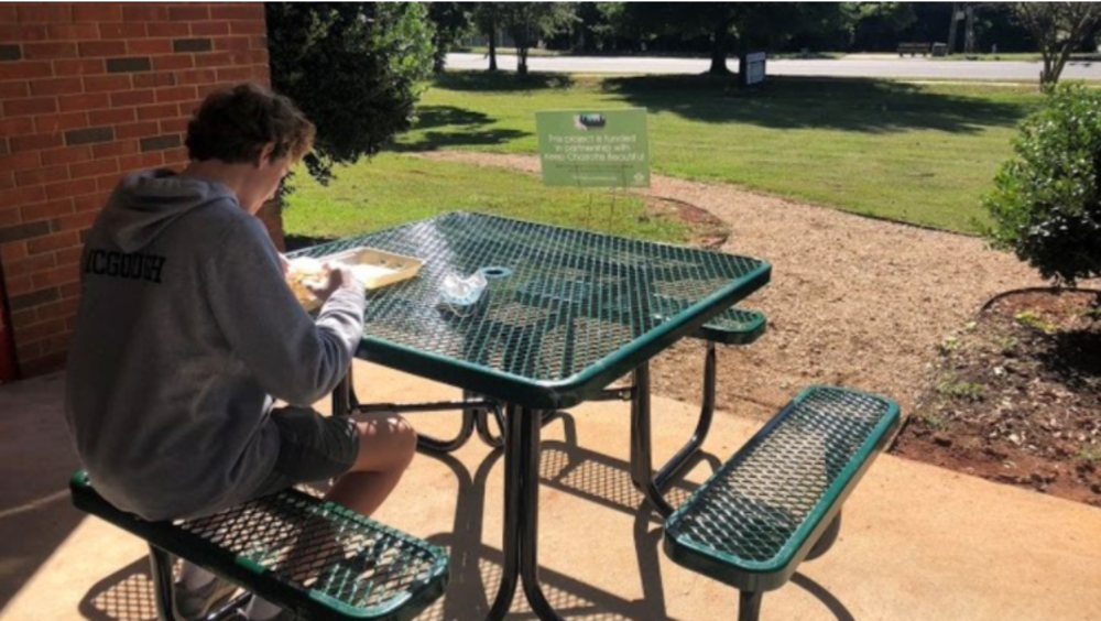 person sitting outside at a new metal table