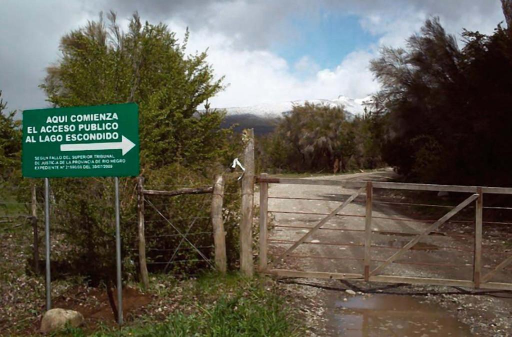 La route Tacuifi menant à Lago Escondido, maintenant bloquée à l'accès public, se trouve au km 92 sur la route 40 en Argentine. Le panneau mentionne la décision de 2009 de la Cour Suprême exigeant l'ouverture au public de la route encore fermée
