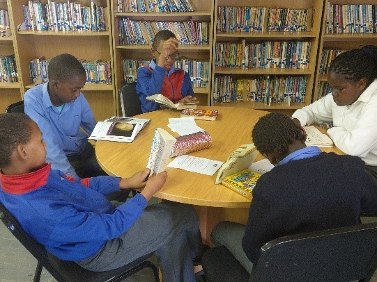 Photo of students participating in a reading program at Mondessa Youth Opportunities, an organization dedicated to educating high-achieving learners from disadvantaged socio-economic backgrounds in Nambia.