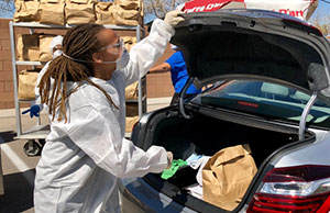 A volunteer loading food into the trunk of a car at a food drive in Las Vegas organized by Culinary Workers Union Local 226.