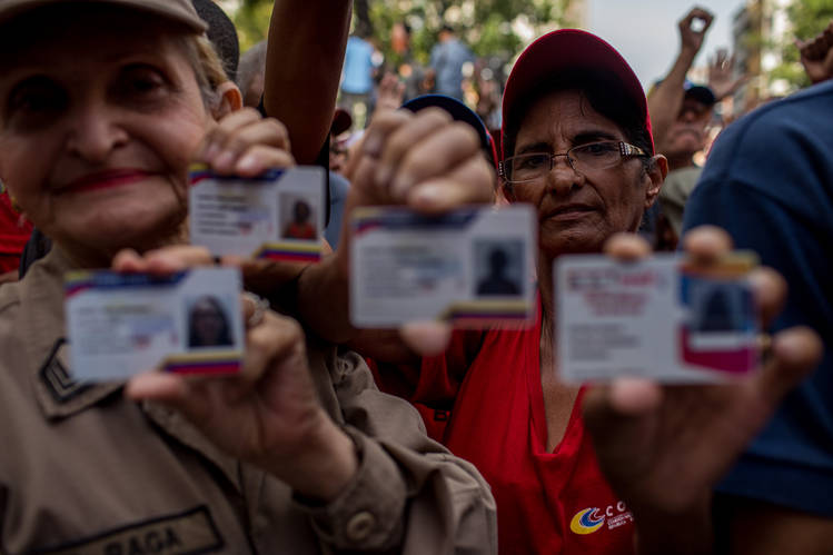 Venezuelans show off their identity cards in Caracas last August.
