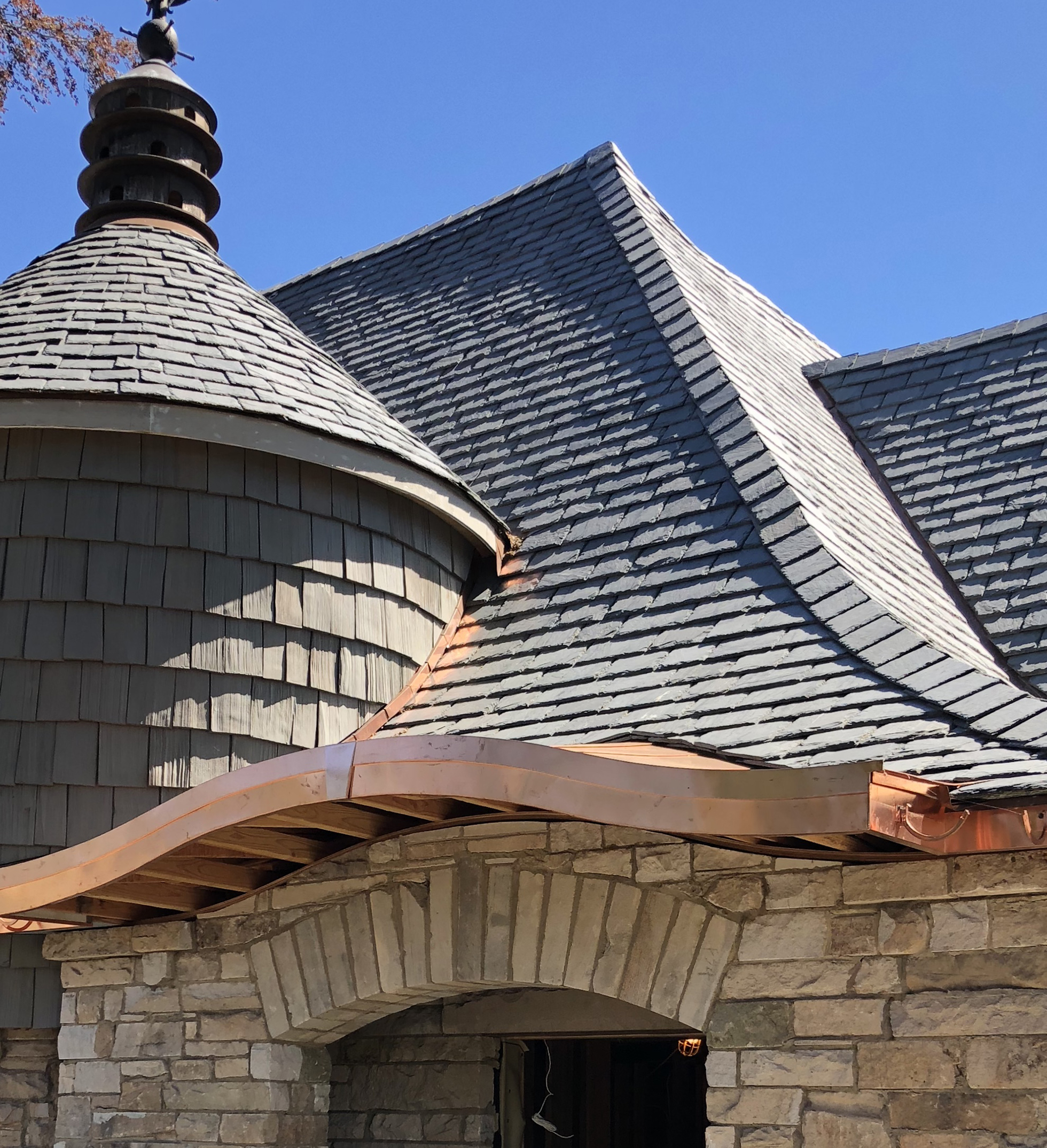 Black roof on stone brick home with copper gutters