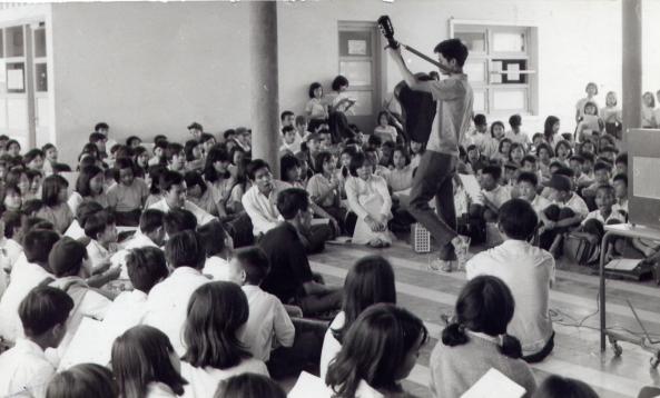Nhạc sĩ Nguyễn Đức Quang (cầm đàn) trong một buổi sinh hoạt của nhóm Du Ca với các học sinh trường Trung Học Kiểu Mẫu Thủ Đức vào cuối thập niên 1960