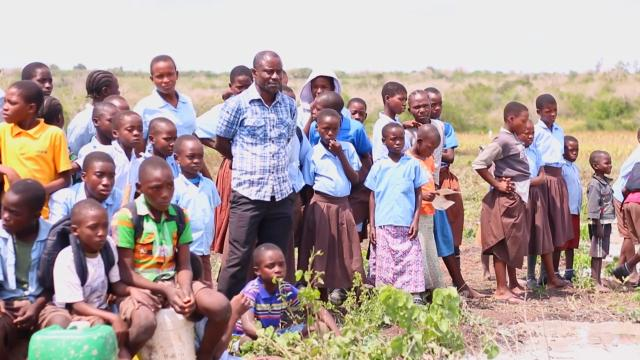 Emmanuel Baya stands in a Kenyan field surrounded by children.