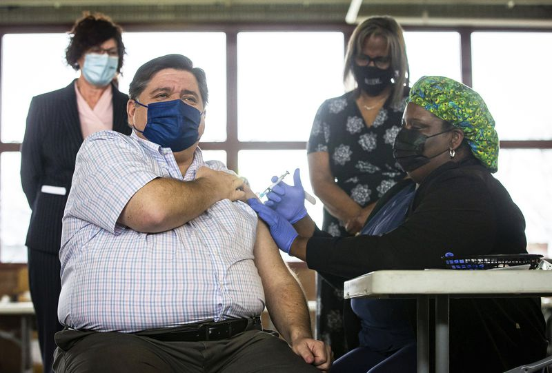 Gov. J.B. Pritzker receives the Johnson & Johnson COVID-19 vaccine from registered nurse NaTasha McCoy on March 24, 2021, at the state-supported mass vaccination site in the Orr Building at the Illinois State Fairgrounds in Springfield.