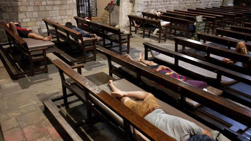 Varios jóvenes migrantes, algunos de ellos menores, durmiendo en los bancos de la Iglesia Santa Anna de Barcelona