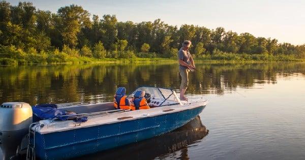 man standing on fishing bot in water