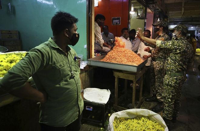 Indian municipal officers interact with a shopkeeper after he is fined for not wearing a face mask at a wholesale flower market ahead of the Hindu festival of Dussehra, in Bengaluru, India, Friday, Oct. 23, 2020. Health officials have warned about the potential for the coronavirus to spread during the upcoming religious festival season, which is marked by huge gatherings in temples and shopping districts. (AP Photo/Aijaz Rahi)
