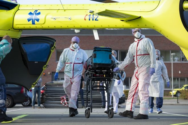 A COVID-19 patient is being carried into a helicopter at Flevoziekenhuis, or FlevoHospital, in Almere, Netherlands, Friday, Oct. 23, 2020. In the latest sign of the scale of the coronavirus pandemic sweeping across Europe, a helicopter is scheduled to start airlifting COVID-19 patients from the Netherlands to an intensive care unit in the German city of Muenster.(AP Photo/Peter Dejong)