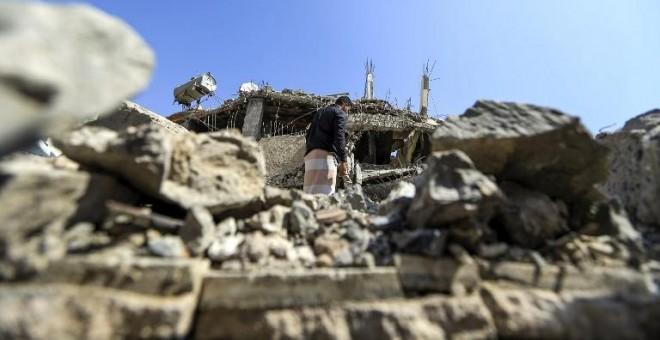 Un hombre busca entre los escombros de un edificio derruido tras un ataque aéreo de Arabia Saudí en Saná, la capital de Yemen. - AFP