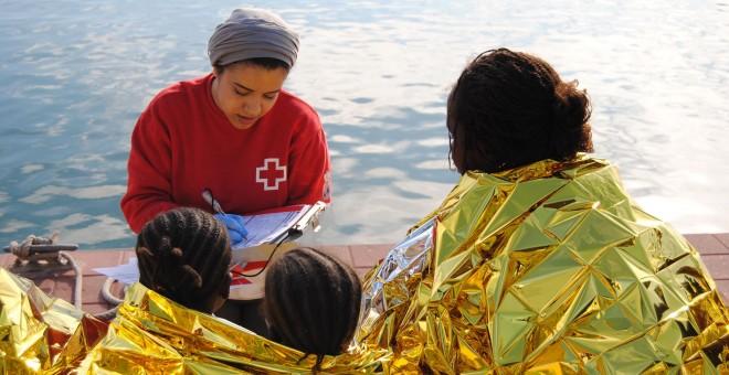 Una imagen de archivo niñas menores a su llegada a Melilla, siendo asistidas por una trabajadora de Cruz Roja tras ser rescatadas de una patera. IRENE QUIRANTE