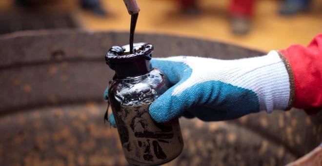 Un trabajador toma una muestra de petróleo en un pozo operado por la compañía petrolera estatal PDVSA en Morichal, Venezuela. REUTERS/Carlos Garcia Rawlins