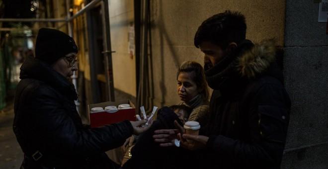 Una vecina voluntaria reparte café a una familia de solicitantes de asilo procedentes de Venezuela en las puertas del Samur Social de Madrid.- JAIRO VARGAS