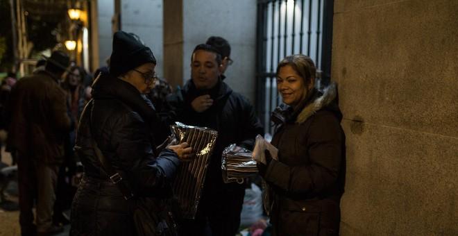 Una voluntaria reparte bufandas entre los solicitantes de asilo que esperan en las puertas del Samur Social de Madrid un plaza para pasar la noche.- JAIRO VARGAS