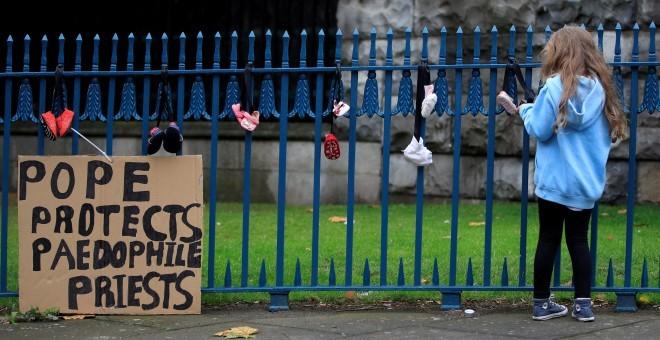 Una niña cuelga un zapato de bebé en una valla para protestar contra los abusos de la Iglesia. - REUTERS