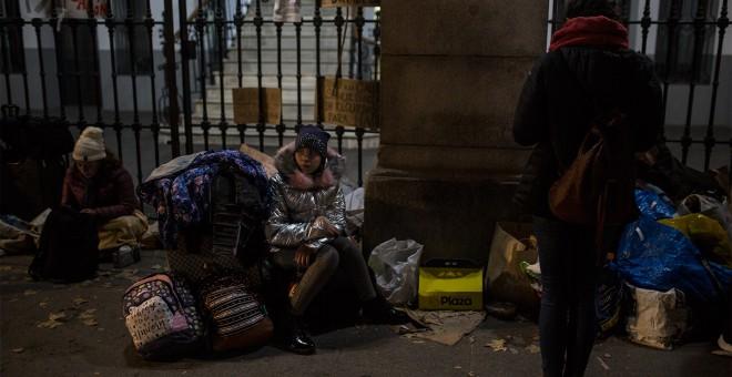Una niña espera sentada sobre sus maletas a que los trabajadores del Samur Social de Madrid confirme si su familia, procedente de Georgia, tendrá plaza en un albergue para pasar la noche mientras formalizan su solicitud de protección internacional.- JAIRO