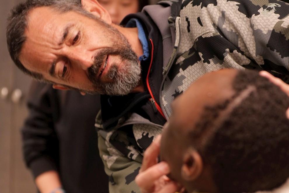 El cirujano Pedro Cavadas observa la cara de Emmanuelle, el niño congoleño de 10 años al que ha extirpado un tumor cráneo facial no maligno   EFE