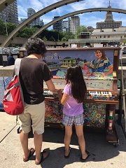 A mother and child play the piano located in front of the Nathan Phillips Square fountain and pool