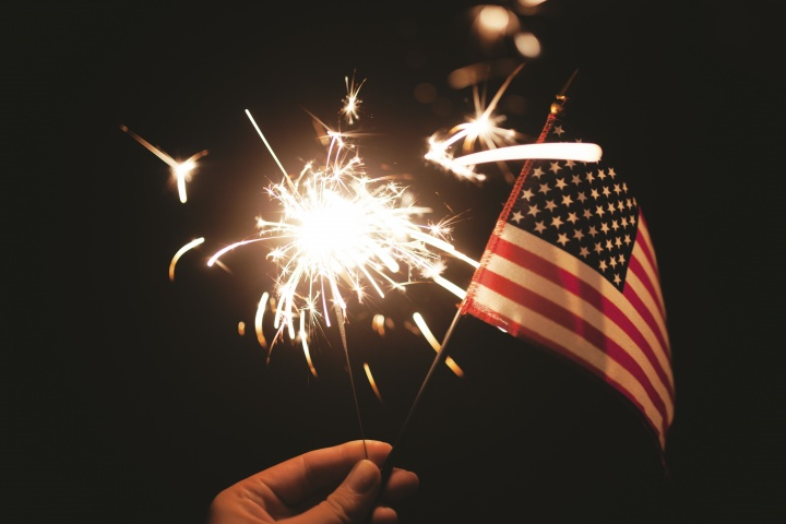 A person holding a sparkler and a small American flag.
