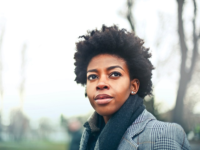 a potrait shot of an African american woman with a black scarf and checkered jacket